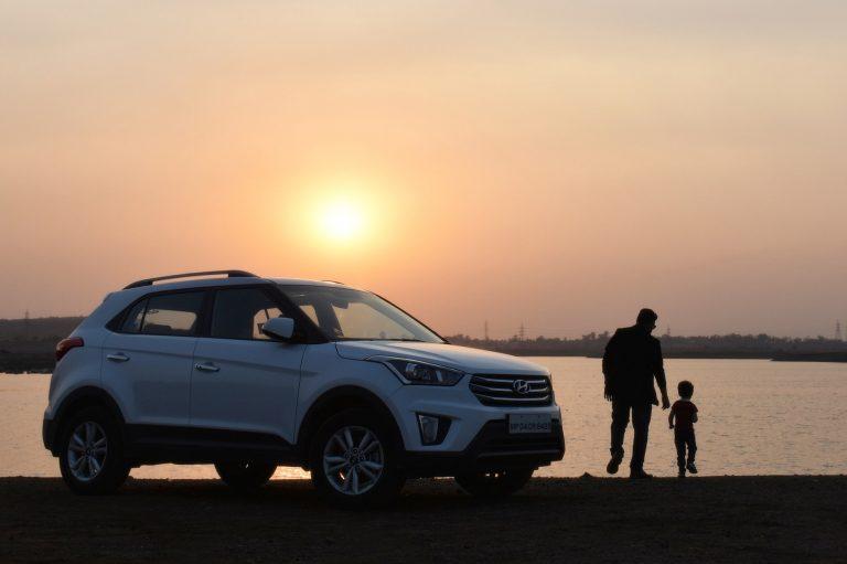 man and boy looking at lake next to vehicle
