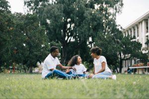 family sitting on grassy field