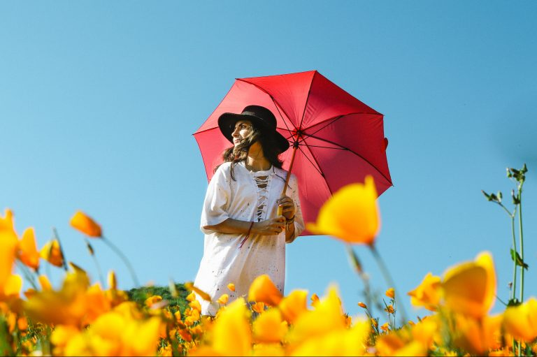woman with red umbrella in a field of flowers
